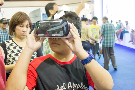 BANGKOK, THAILAND - October 5, 2014  :The  Man ues the Samsung Galaxy Note 4 and Samsung Galaxy  Gear VR, is an Android smartphone produced by Samsung Electronics at Thailand Mobile Expo 2014
