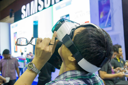 samsung galaxy: BANGKOK, THAILAND - October 5, 2014  :The  Man ues the Samsung Galaxy Note 4 and Samsung Galaxy  Gear VR, is an Android smartphone produced by Samsung Electronics at Thailand Mobile Expo 2014