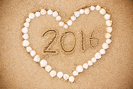 2016 inscription written in the wet yellow beach sand with Heart-shaped shell. Concept of celebrating the New Year