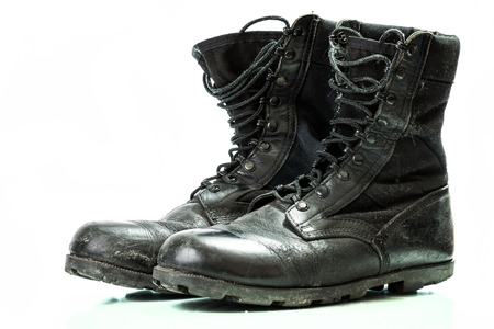 protective work wear: Black old combat military boots isolated on white background Stock Photo
