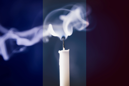 carnage: Pray for Paris 13 November 2015, Candle light with  France flag and message.