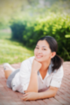 blur effect: Blur effect of young asian woman relaxing outdoors looking happy and smiling