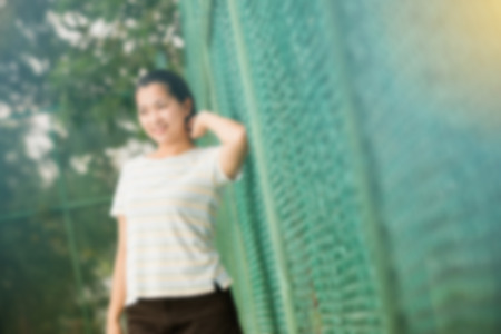 tennis skirt: Blur effect of asian female relax and smile standing on tennis court and looking at camera