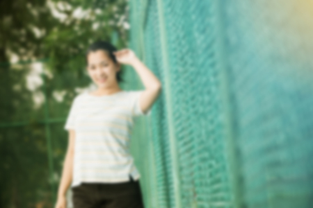 blur effect: Blur effect of asian female relax and smile standing on tennis court and looking at camera