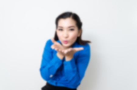 blue face: Blur effect of image of a young woman with a lovely look and charming smile in blue shirt