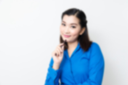 Blur effect of image of a young woman with a lovely look and charming smile in blue shirt