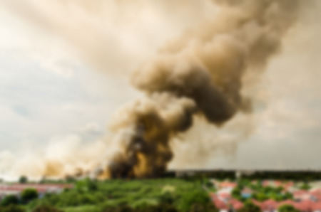 Blur effect of Forest fires in the city, causing a large flame and smoke in the air is very hot days. Firemen rush to help prevent the spread of fire to the village Stock Photo
