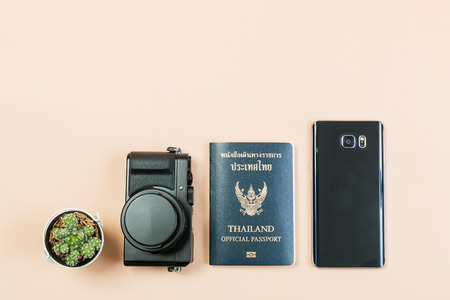 Flat lay and copy space for design work of vintage digital compact camera with Thailand official passport and smart phone and small cactus on yellow pastel color background. Stock Photo