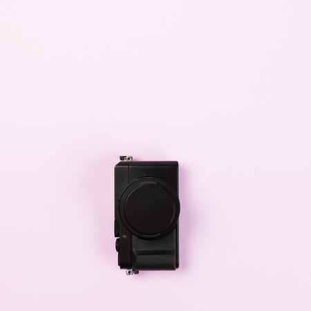 Vintage digital compact camera on pink pastel color background with flat layout and copy space for design work