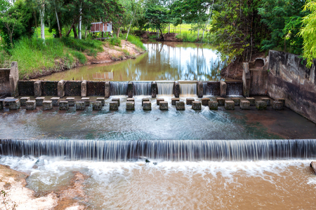 Weir or dam to slow down the flow of water in the river. There are fresh green areas in Thailand. Stock Photo