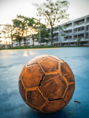 Old yellow soccer ball on the blue football field on the day of sunrise.