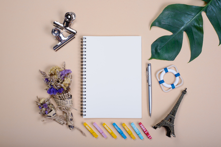 Flat lay empty book and pen, clip, dry flower and green leaf for design work on yellow pastel color background.
