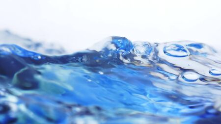 Soft blur focus of Abstract water splash surface filling the frame with the water drop and waving liquid with an air bubble on a white background and copy space
