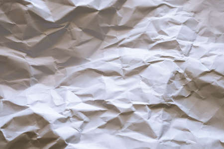 The white paper is wrinkled with a shadow and selective focus texture background.
