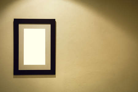 Vintage photo frame on the warm wall with a light focus shape and copy space