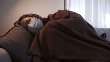 Young Asian woman suffering from coronavirus has black eyes chills all over her body gets cold and uses a mask and blanket to keep warm on the sofa in her separate living room and quarantine