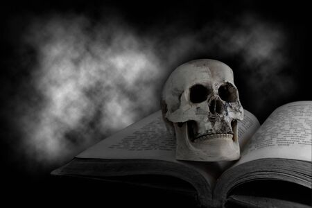 Skull on the old book with horrible of dark clouds background. Фото со стока