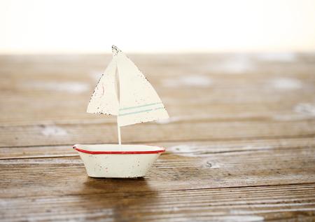 木製のテーブルにブリキの白い帆船