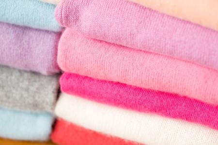 Stapel warme roze, paarse, witte, lichtblauwe, grijze, rode en oranje gezellige truien.