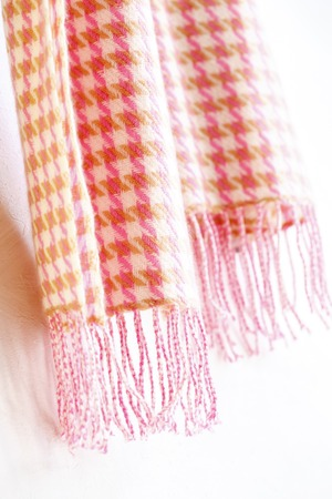 Warm knitted muffler pink hound's-tooth check isolated on white