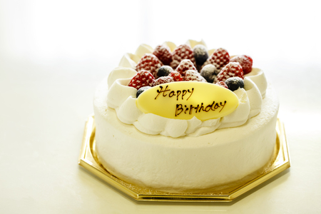 White cake decorated with strawberries and blueberries placed on a tray on a white table.