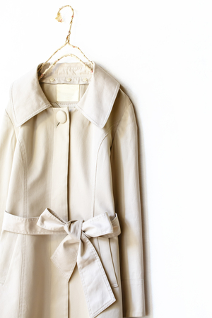 A beige or greige elegant trench coat with ribbon isolated over white.Close up