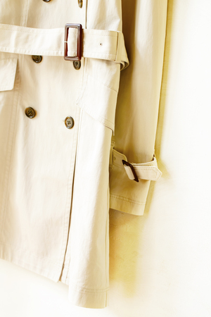 A beige elegant trench coat with belt and sleeve isolated over white.Close up