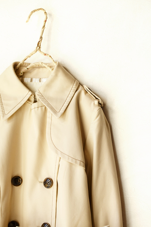 A beige elegant trench coat isolated over white. Close up