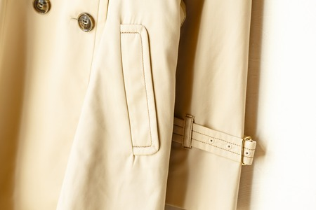 A beige elegant trench coat with sleeve and pocket isolated over white.Close up