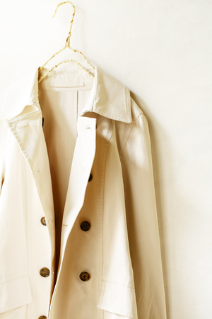 A beige or greige elegant trench coat isolated over white. opened in front. Close up