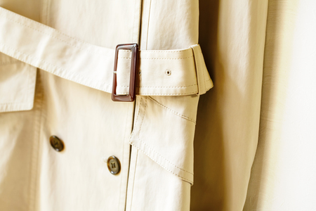A beige elegant trench coat with belt isolated over white.Close up Stock Photo