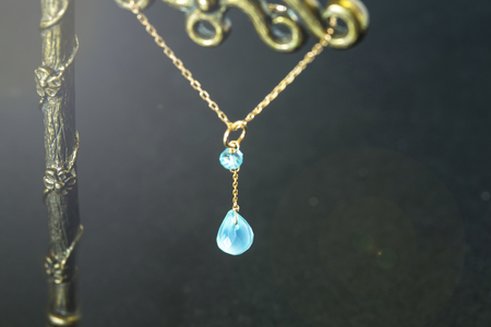 golden necklace with apatite with green chalcedony with blue topaz on black background.close up. Stock Photo