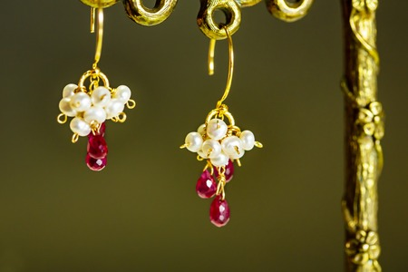 golden earrings with red rubies with white pearls on black background.close up. Stock Photo