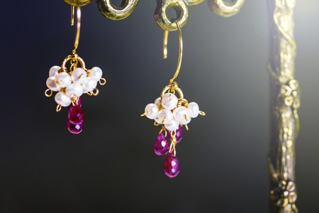 golden earrings with red rubies with white pearls on black background.close up.