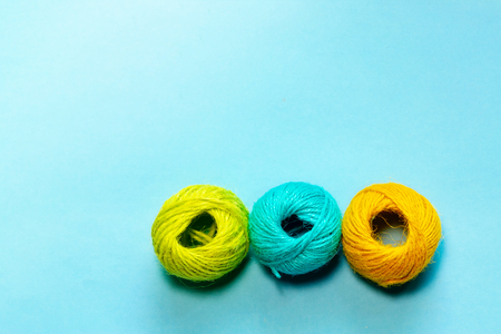 Set of yellowish green, orange and blue hemp threads isolated on blue color background. Colorful Tones, Flat lay. copy space for your text Stock Photo
