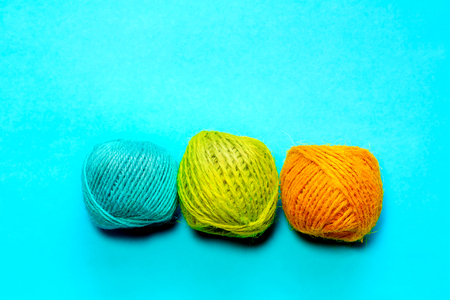 Set of yellowish green, orange and blue hemp threads isolated on blue color background. Colorful Tones, Flat lay. copy space for your text Banco de Imagens