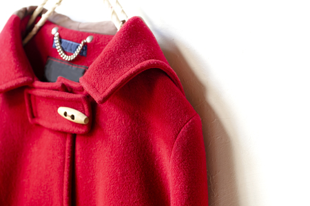 red wool coat hanging on clothes hanger on white background.Close up Stockfoto