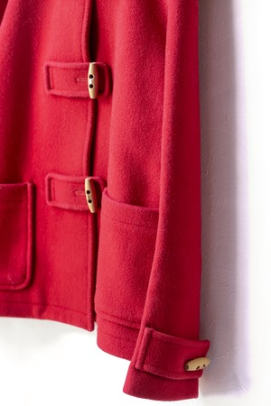 red wool coat hanging on clothes hanger on white background.Close up Reklamní fotografie