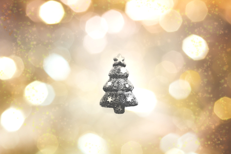 black christma tree outline on gold, yellow, white, black, and grey color bokeh background. Christmas and showy image.
