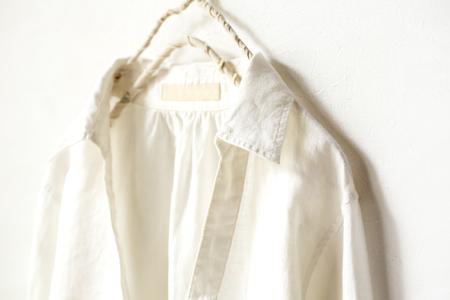 una camicetta o una camicia in bianco che appende sulla gruccia su priorità bassa bianca. Primo piano.