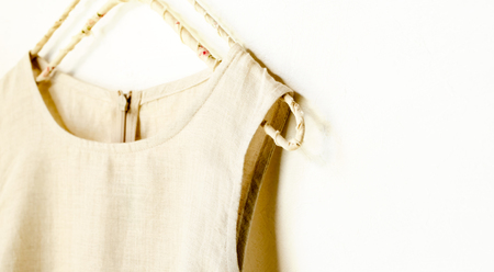 a no sleeve in beige hanging on a hanger in a white background.Close up