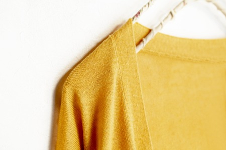 a cardigan in yellow hanging on clothes hanger on white background.Close up. Stock Photo