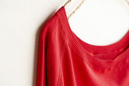 a cut sew or knit in red hanging on clothes hanger on white background.Close up. Stock Photo
