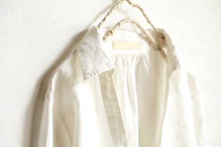 a blouse or shirt in white hanging on clothes hanger on white background.Close up.