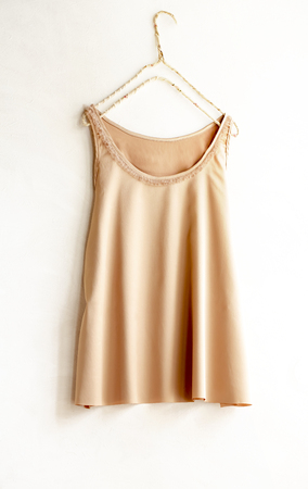orange beige tank top hanging on a hanger in a white wall.Close up Banco de Imagens