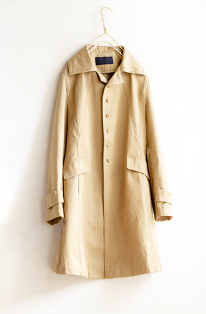 A beige trench coat isolated over white. Close up Banco de Imagens