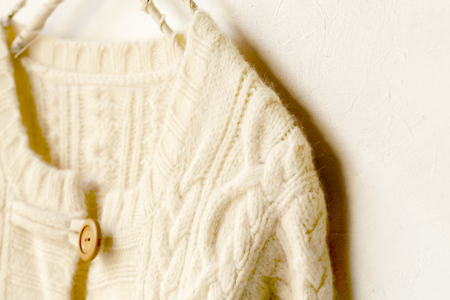 a thick knitted cardigan in white hanging on clothes hanger on white background. Close up.