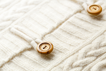 Background texture of white pattern knitted fabric made of cotton or wool and wooden button. closeup.