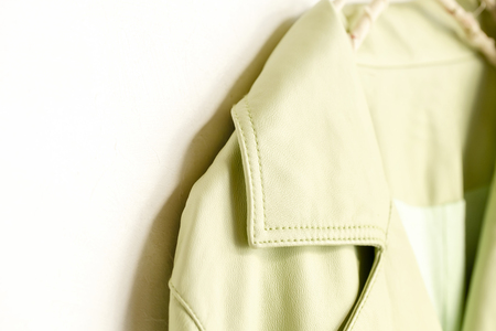 Yellowish green Jacket of the real leather hanging on clothes hanger on white background.close up.