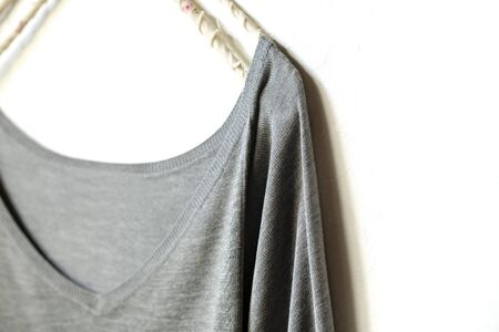 a cut sew or knit in grey hanging on clothes hanger on white background.Close up.